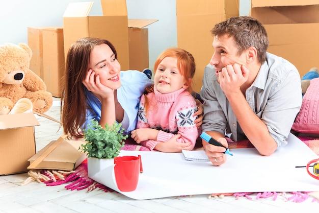 Die glückliche familie bei reparatur und umzug. die familie, die eine unterkunft vor dem hintergrund von kisten plant