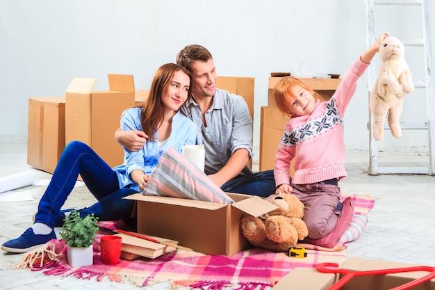 Die glückliche familie bei reparatur und umzug. die familie plant die unterbringung auf einer der boxen
