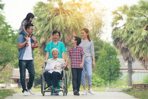 Die glückliche familie, die am park an einem sonnigen tag, großfamilie aufwirft, entspannen sich draußen lächeln