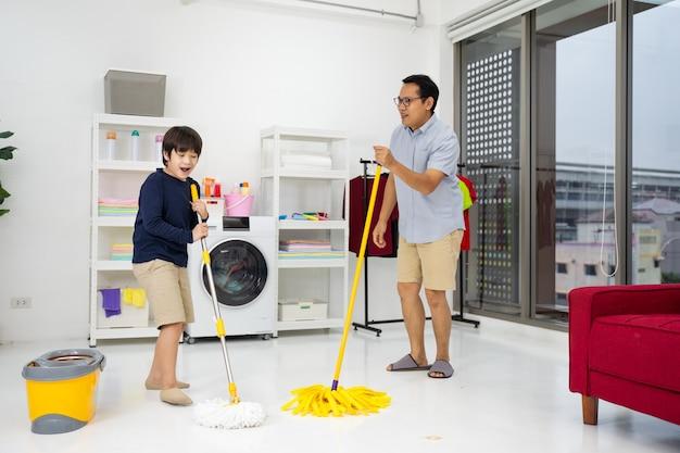 Die glückliche familie putzt das zimmer. asiatischer vater und sohn putzen das haus