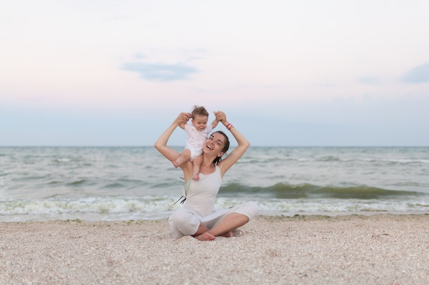 Die glückliche familienmutter- und -kindertochter, die yoga tut, meditieren in lotussitz auf strand bei sonnenuntergang