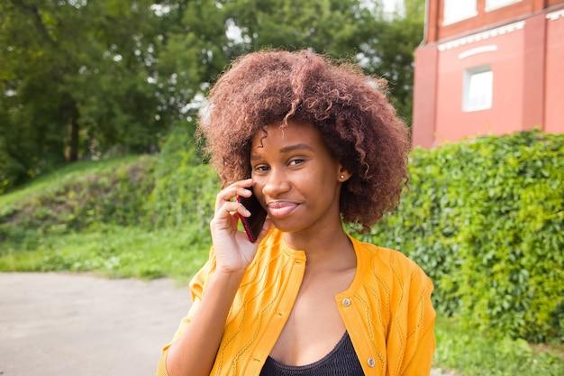 Die glückliche frau auf der straße telefoniert