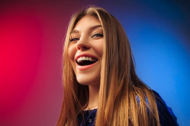 Die glückliche frau, die gegen farbigen raum steht und lächelt.