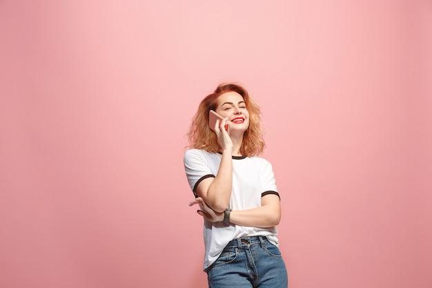 Die glückliche frau lächelt und spricht auf dem smartphone gegen rosa wand.