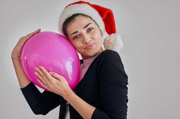 Die glückliche frau mit weihnachtsmütze, die den ballon hält