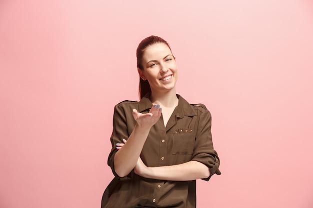 Die glückliche geschäftsfrau, die gegen rosa wand steht und lächelt.