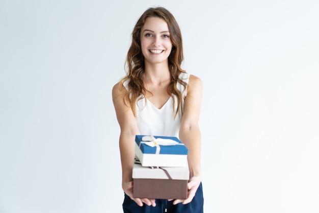 Die glückliche hübsche frau, die zwei geschenkboxen mit band hält, beugt