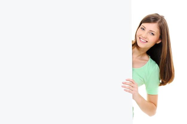 Die glückliche junge frau der schönheit schaut aus dem großen leeren banner heraus