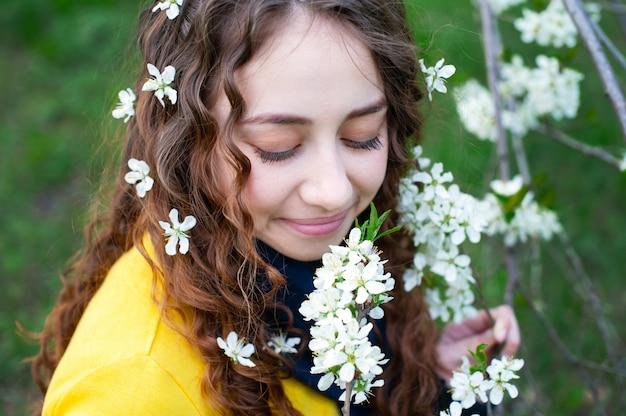 Die glückliche junge frau, die geruch genießt, blüht über frühlingsgarten
