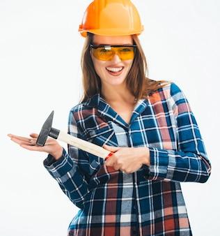 Die glückliche junge frau trägt einen orangefarbenen schutzhelm, eine gelbe brille und ein kariertes hemd