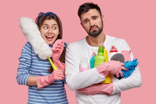 Die glückliche junge hausfrau und ihr mann machen zusammen einen frühjahrsputz, verwenden verschiedene reinigungsmittel und bürsten