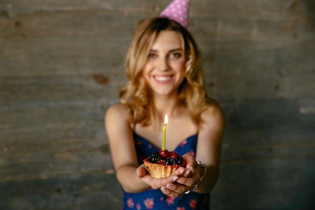 Die glückliche lächelnde junge frau, die ihre geburtstagsfeier feiert, hält einen fruchtkleinen kuchen mit kerze