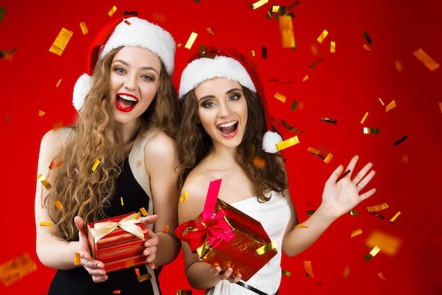 Die glückliche lächelnde junge schönheitsfrau, die märchen santa christmas-hut wenig schwarzes weißes kleid feiert winterurlaubpartei-griffgeschenke feiert, lokalisierte konfettis