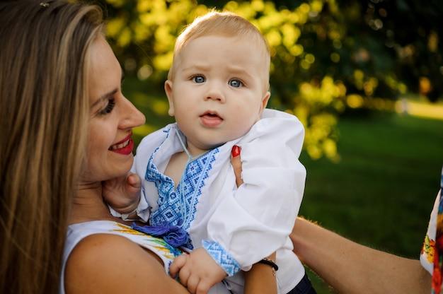 Die glückliche mutter, die an hände ein baby hält, kleidete im gestickten hemd an