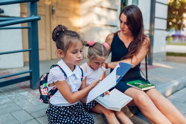 Die glückliche mutter lernte die töchter ihrer kinder nach dem unterricht kennen.