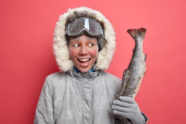 Die glückliche schöne frau, die mit frost bedeckt ist, genießt die winterzeit und das angeln verbringt die freizeit im freien, gekleidet in warme oberbekleidung während des kalten frostigen tages.