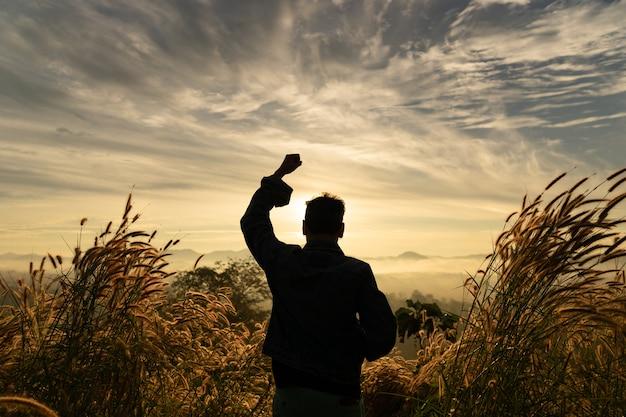 Die glückliche stellung des schattenbildmannes mit den händen steigen oben auf berg mit sonnenaufganghimmel.
