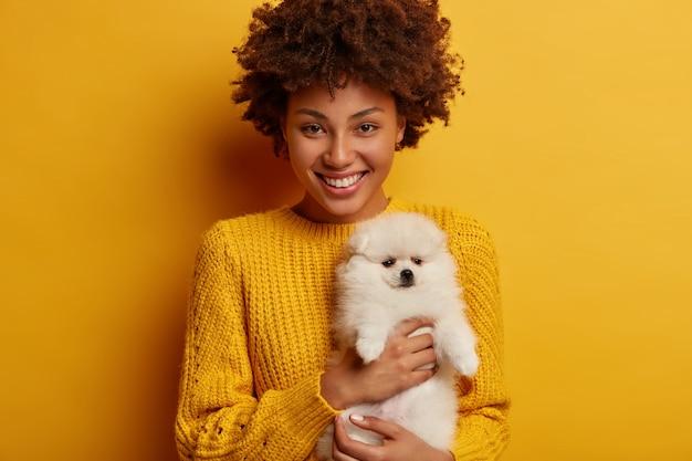Die glückliche tierbesitzerin ist gut gelaunt, nachdem sie mit einem welpen den tierarzt besucht hat. sie findet heraus, dass ihr spitzhund gesund ist und einen gelben strickpullover trägt