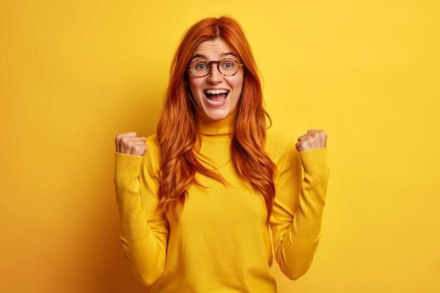 Die glückliche überglückliche frau hat das gefühl, dass der gewinner über etwas jubelt, das die fäuste hebt, und ruft aus: ja, die gewinnergeste freut sich über den sieg.