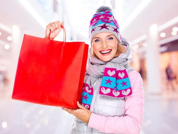 Die glückliche weiße frau mit geschenken nach dem einkaufen