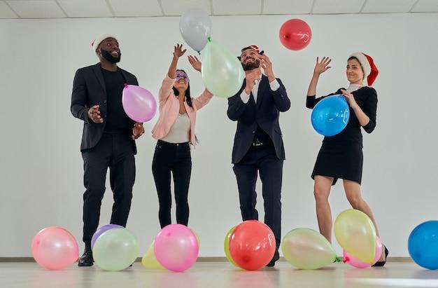 Die glücklichen geschäftsleute, die mit ballons spielen