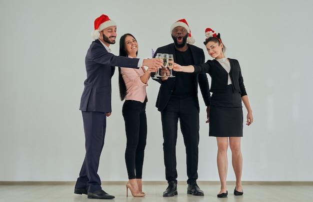 Die glücklichen geschäftsleute in weihnachtsmütze trinken champagner