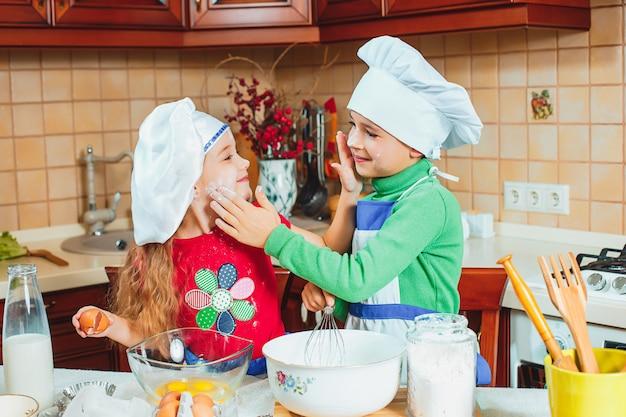 Die glücklichen zwei lustigen kinder bereiten den teig vor, backen kekse in der küche