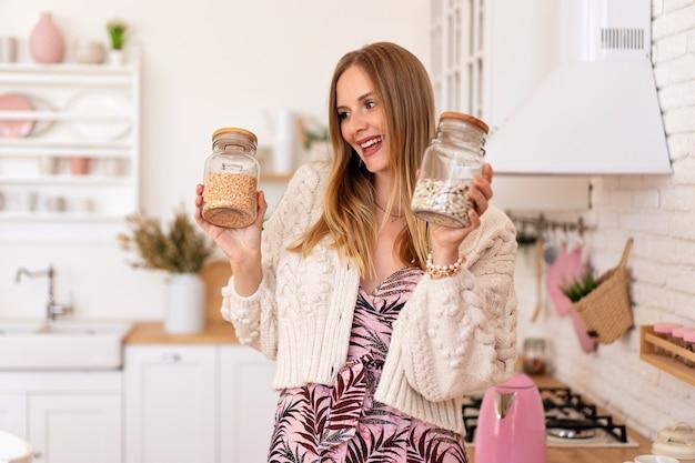 Die glückselige hübsche blonde frau legt in ihrer gemütlichen küche sachen und ordnung und organisiert sachen Kostenlose Fotos