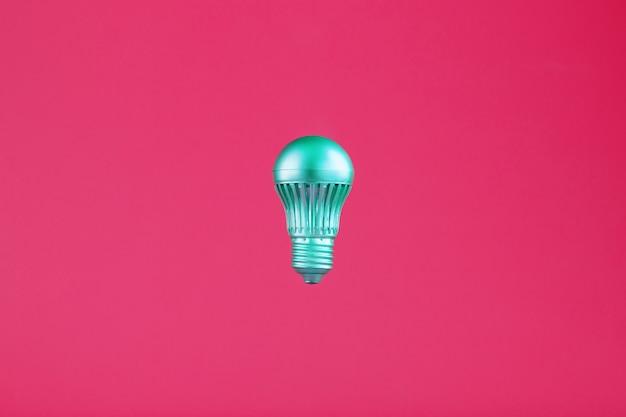 Die glühbirne schwebt in der mitte des rahmens in einem isolierten raum auf pink.