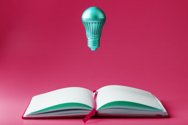 Die glühbirne schwebt über den offenen seiten eines leeren notizbuchs in pink.