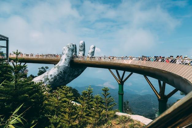 Die goldene brücke wird von zwei riesigen händen im fremdenverkehrsort auf ba na hill in danang, vietnam, gehoben. das bergresort ba na hill ist ein beliebtes ziel für touristen, die das wahrzeichen zentralvietnams besuchen