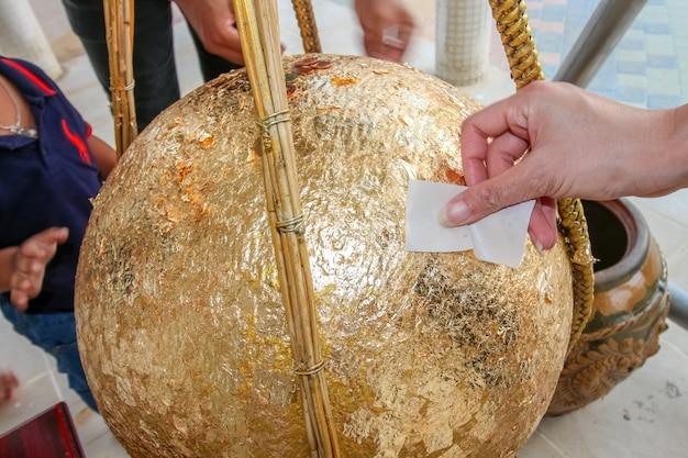 Die goldene steinschnitzerei ist eine kugel namens loknimit, die in ein blatt gold und eine münze eingelegt wurde. im tempel