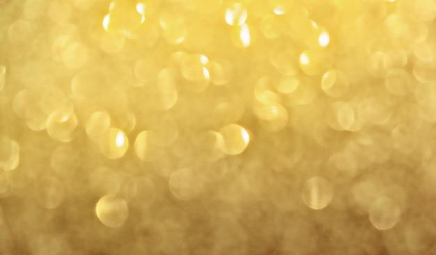 Die goldene textur des glitzerpapiers reflektierte den hellen bokeh-hintergrund