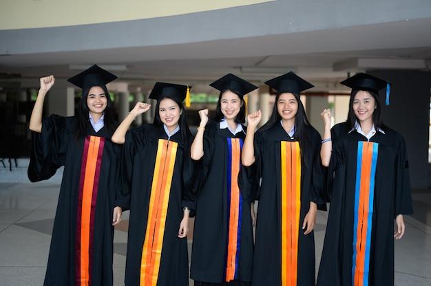 Die graduierende studentengruppe trug bei der abschlussfeier der universität einen schwarzen hut.