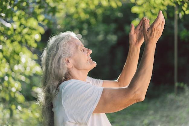 Die grauhaarige großmutter betet draußen.