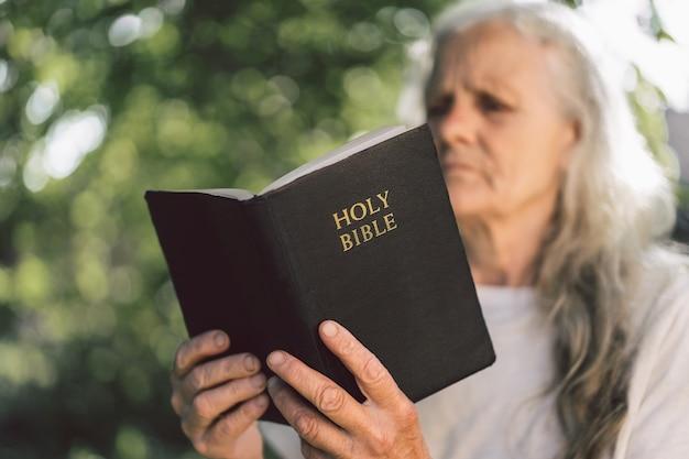 Die grauhaarige großmutter hält die bibel in den händen.