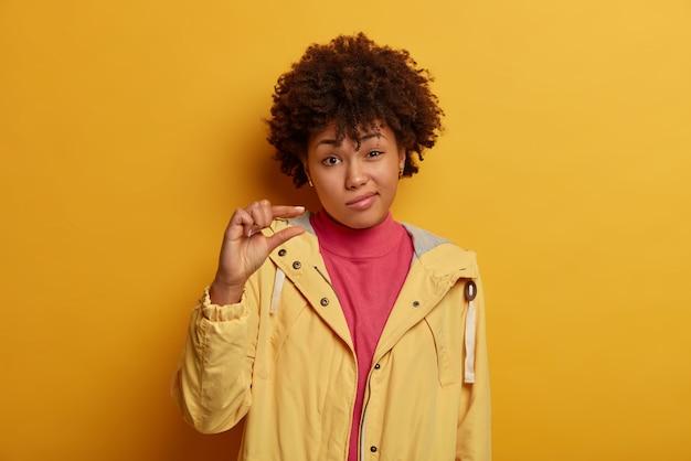 Die größe ist wichtig. unbekannt dunkelhäutiges weibliches model formt etwas sehr winziges und sagt, das ist alles, spitzt lippen, trägt gelbe jacke