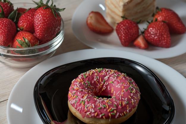 Die großaufnahme des vorderen rosa erdbeer-donuts, der mit buntem verziert wird, besprüht