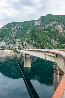 Die große brücke wird von einem malerischen bergsee überquert.