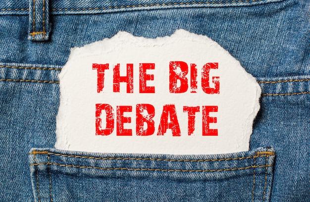 Die große debatte auf weißem papier in der tasche einer blue denim-jeans