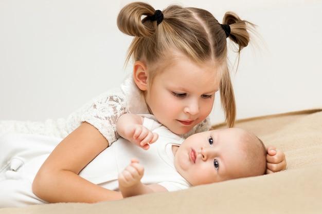 Die große schwester umarmt und spricht mit ihrem kleinen bruder mit liebe