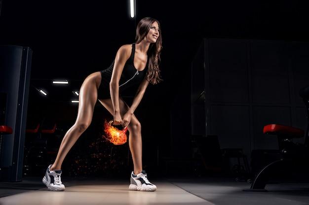 Die große sportliche frau lächelt und trainiert im fitnessstudio mit einer feurigen kettlebell