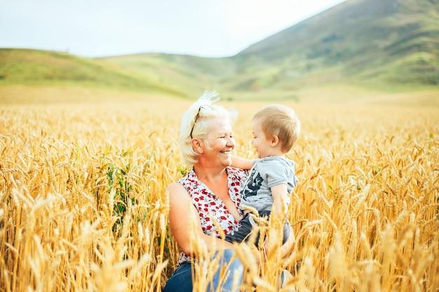 Die großmutter hält die hand eines kleinen jungen auf unschärfehintergrund.