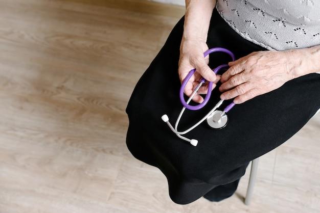 Die großmutter hält ein stethoskop in der hand