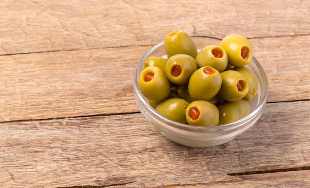 Die grünen oliven in der schüssel auf hölzernem hintergrund.