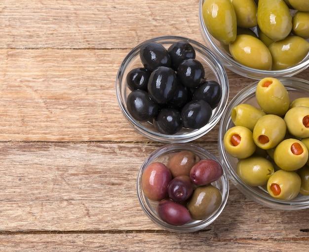 Die grünen und schwarzen oliven in der schüssel auf hölzernem hintergrund.