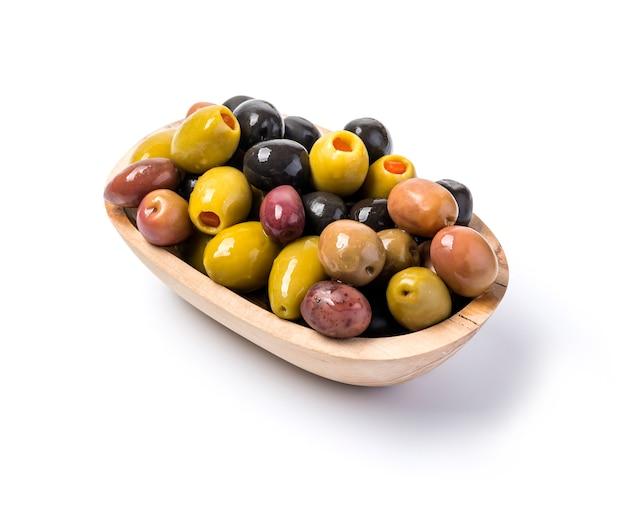 Die grünen und schwarzen oliven in der schüssel auf weißem hintergrund.