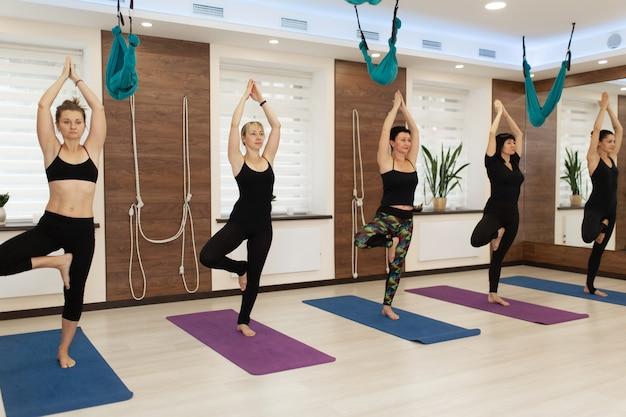 Die gruppe der frau, die yoga tut, trainiert in der turnhalle. fit und wellness lifestyle