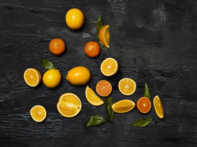 Die gruppe der frischen früchte - zitronen und mandarinen gegen den schwarzen raum