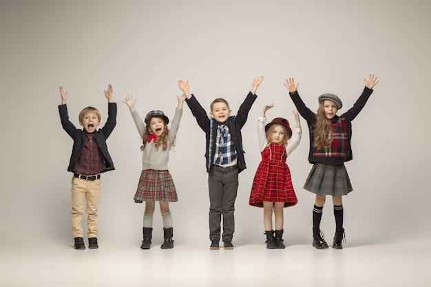 Die gruppe der glücklich lächelnden jugendlich mädchen und jungen auf einem pastell. stilvolle junge teenager-mädchen posieren. klassischer herbststil. teen und kinder modekonzept. kinder-fasion-konzept